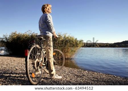 Senior woman riding a bike beside a lake - stock photo