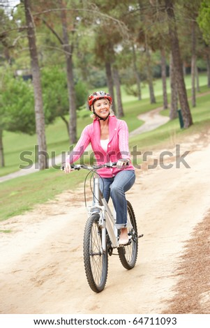 Senior woman riding bicycle in park - stock photo