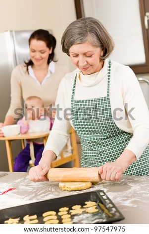 Senior woman rolling dough prepare for baking cookies in kitchen - stock photo