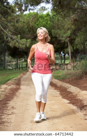 Senior woman running in park - stock photo