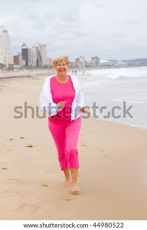 senior woman running on beach for exercise - stock photo