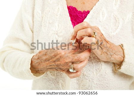 Senior woman's arthritic hands struggling to button her sweater. - stock photo