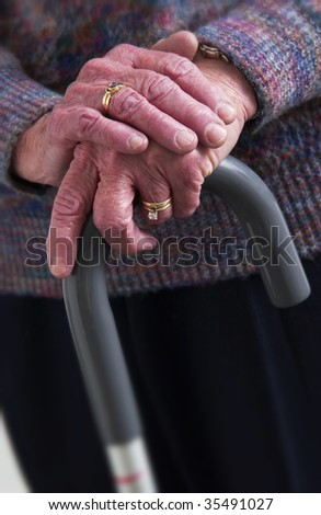 senior woman's hand on cane - stock photo