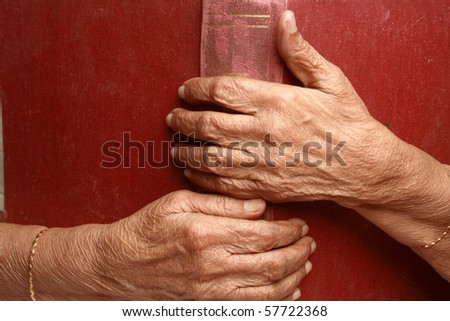 Senior woman's hands holding an old book - stock photo