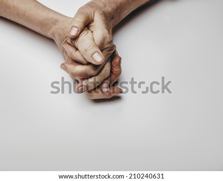 Senior woman's hands isolated on grey background. Hands of a relaxed old female with copy space. Praying hands. - stock photo