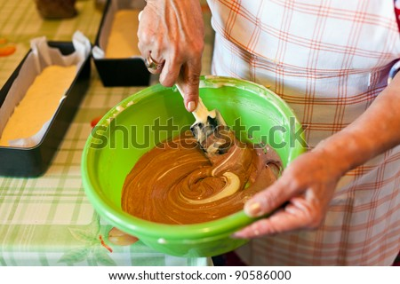 Senior woman's hands stirring a cocoa cream with spatula - stock photo