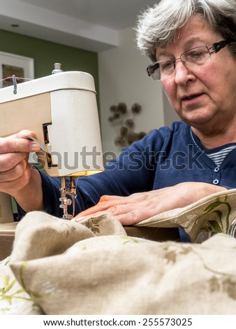 Senior woman sawing linen with sewing machine - stock photo