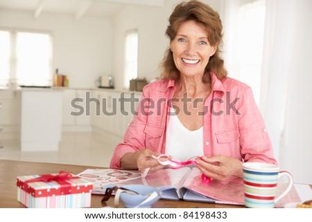 Senior woman scrapbooking - stock photo