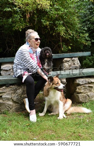 Senior woman seated at picnic table with two dogs on Summer day
