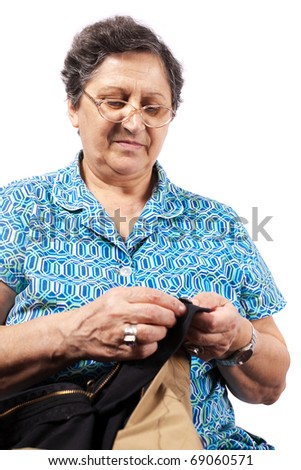 Senior woman sewing buttons on clothing, isolated on white background - stock photo