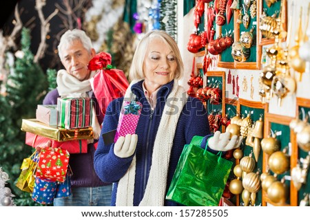 Senior woman shopping Christmas ornaments at store with man holding presents in background - stock photo