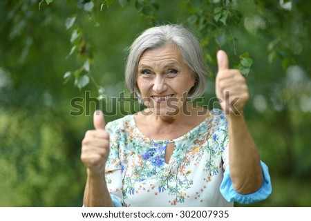 Senior woman showing thumbs up in the park - stock photo