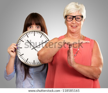 Senior Woman Showing Timeout Sign In Front Of Young Woman Holding Clock On Gray Background - stock photo