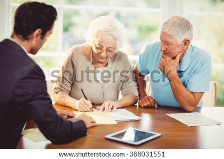 Senior woman signing document at home