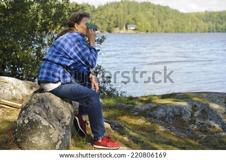 Senior woman sits on a rock by a lake surrounded by forests. She's drinking from a coffee or tea mug.