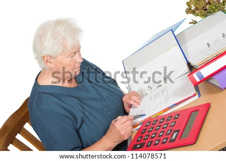Senior woman sitting at her dining table doing her accounts checking her figures in a file with a large calculator alongside her - stock photo