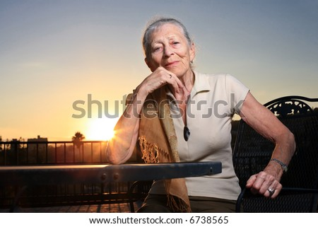 Senior woman sitting at the table outdoors at sunset. - stock photo