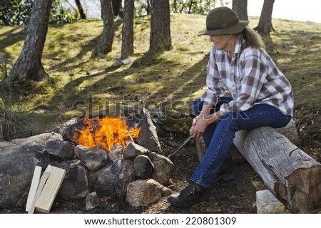 Senior woman sitting by camp fire
