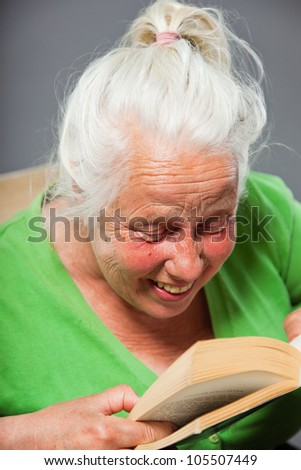 Senior woman sitting chair reading a book. Grey long hair. Studio shot isolated on grey background. - stock photo