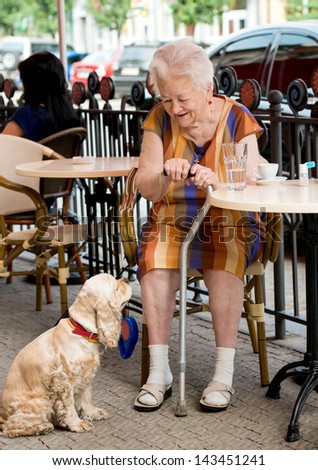 Senior woman sitting in cafe with a dog and having a cup of coffee - stock photo