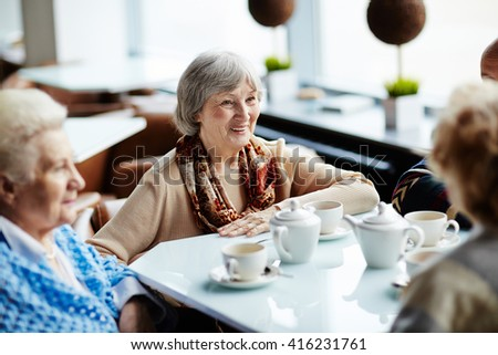 Senior woman sitting in cafe with friends - stock photo