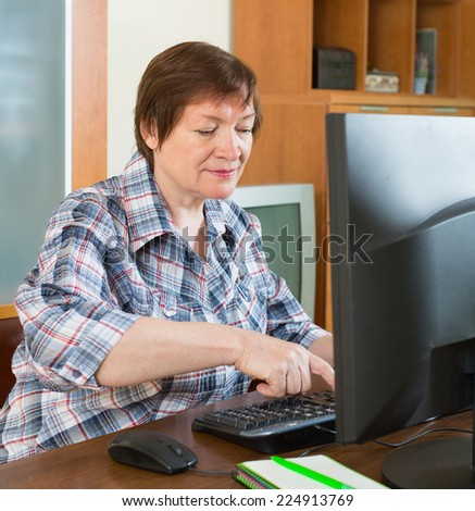 Senior woman sitting in front of PC and using keyboard - stock photo