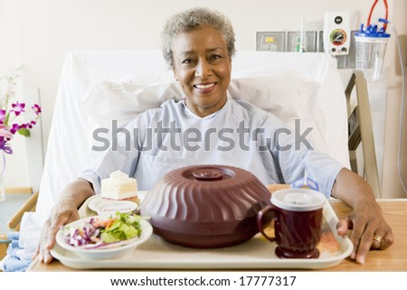 Senior Woman Sitting In Hospital Bed With A Tray Of Food