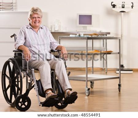 Senior woman sitting in wheelchair - stock photo