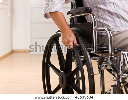 Senior woman sitting in wheelchair - stock photo