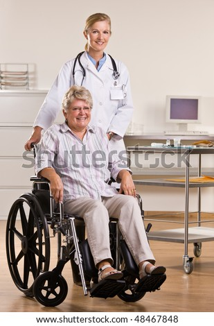 Senior woman sitting in wheelchair with doctor - stock photo