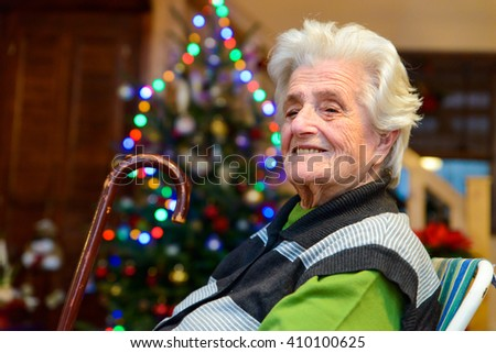 Senior woman sitting near a christmas tree