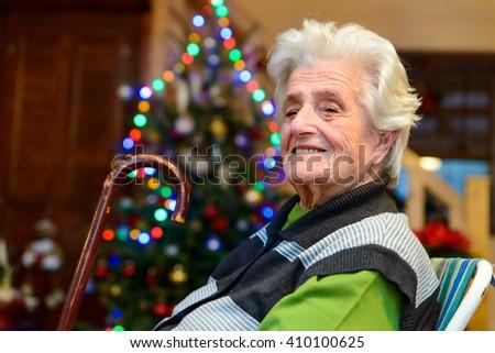 Senior woman sitting near a christmas tree - stock photo