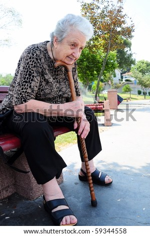 senior woman sitting on a bench by leaning her stick / cane - stock photo