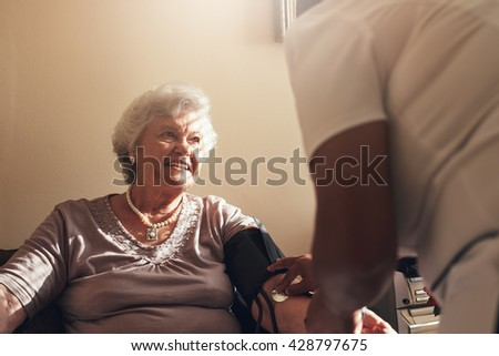 Senior woman sitting on a chair at home with female caregiver checking her blood pressure. Elderly woman getting routine check from a female doctor. - stock photo