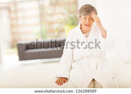 senior woman sitting on bed and having headache - stock photo