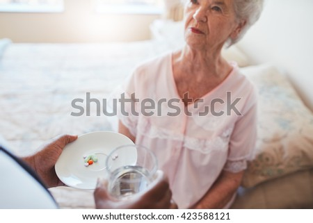 Senior woman sitting on bed and home care nurse giving medication. Hand of nurse giving pills to elderly female patient. - stock photo