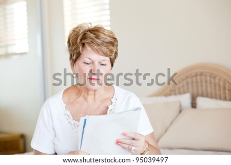 senior woman sitting on bed and reading newspaper - stock photo