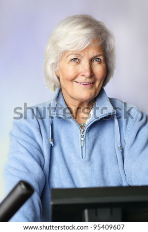 Senior woman sitting on bicycle ergometer - stock photo