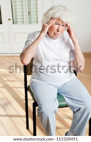 Senior woman sitting on chair suffering from headache - stock photo