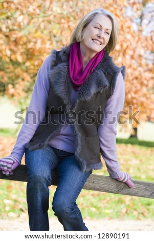 Senior woman sitting on fence with autumn trees behind - stock photo
