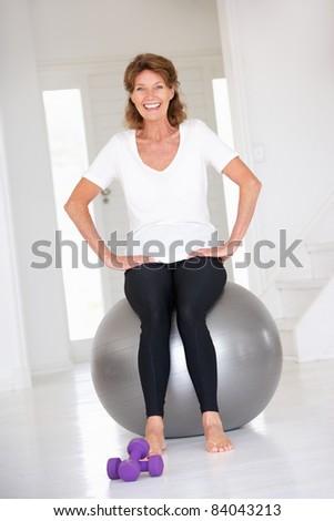 Senior woman sitting on gym ball - stock photo