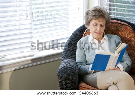 Senior woman sitting on living room chair reading book - stock photo