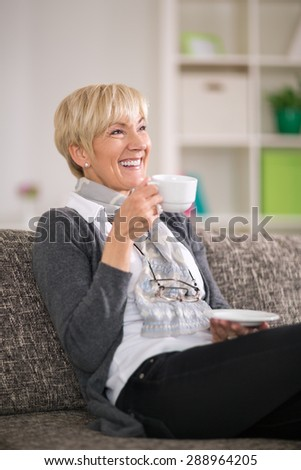 Senior woman sitting on sofa smiling and drinking tea