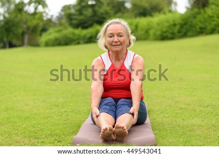 Senior woman sitting on yoga mat outdoors in park with wide open field of green turf grass and copy space - stock photo