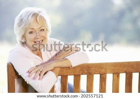 Senior woman sitting outdoors - stock photo