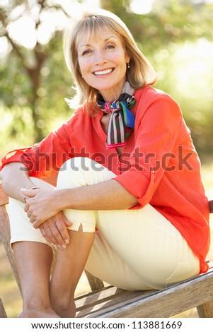 Senior Woman Sitting Outdoors On Bench - stock photo