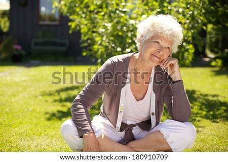 Senior woman sitting outdoors on grass looking away and thinking. Elder woman relaxing in backyard garden day dreaming - stock photo