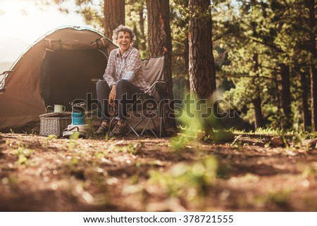 Senior woman sitting relaxed outside a tent. Smiling mature woman camping in forest. - stock photo