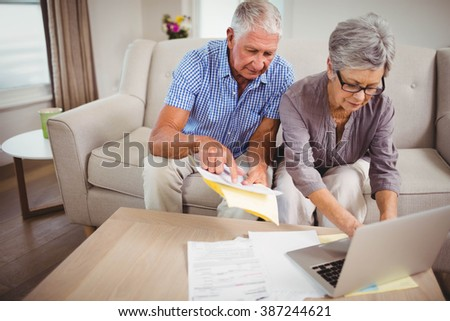Senior woman sitting with man on sofa and paying bills online on laptop in living room - stock photo