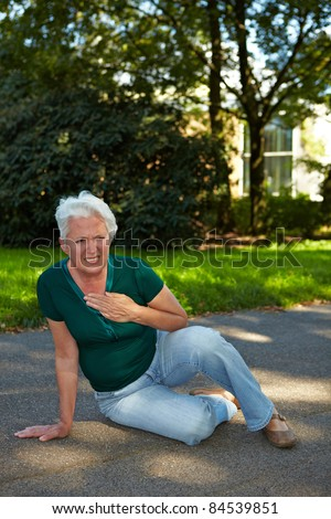 Senior woman sitting with stroke in park - stock photo
